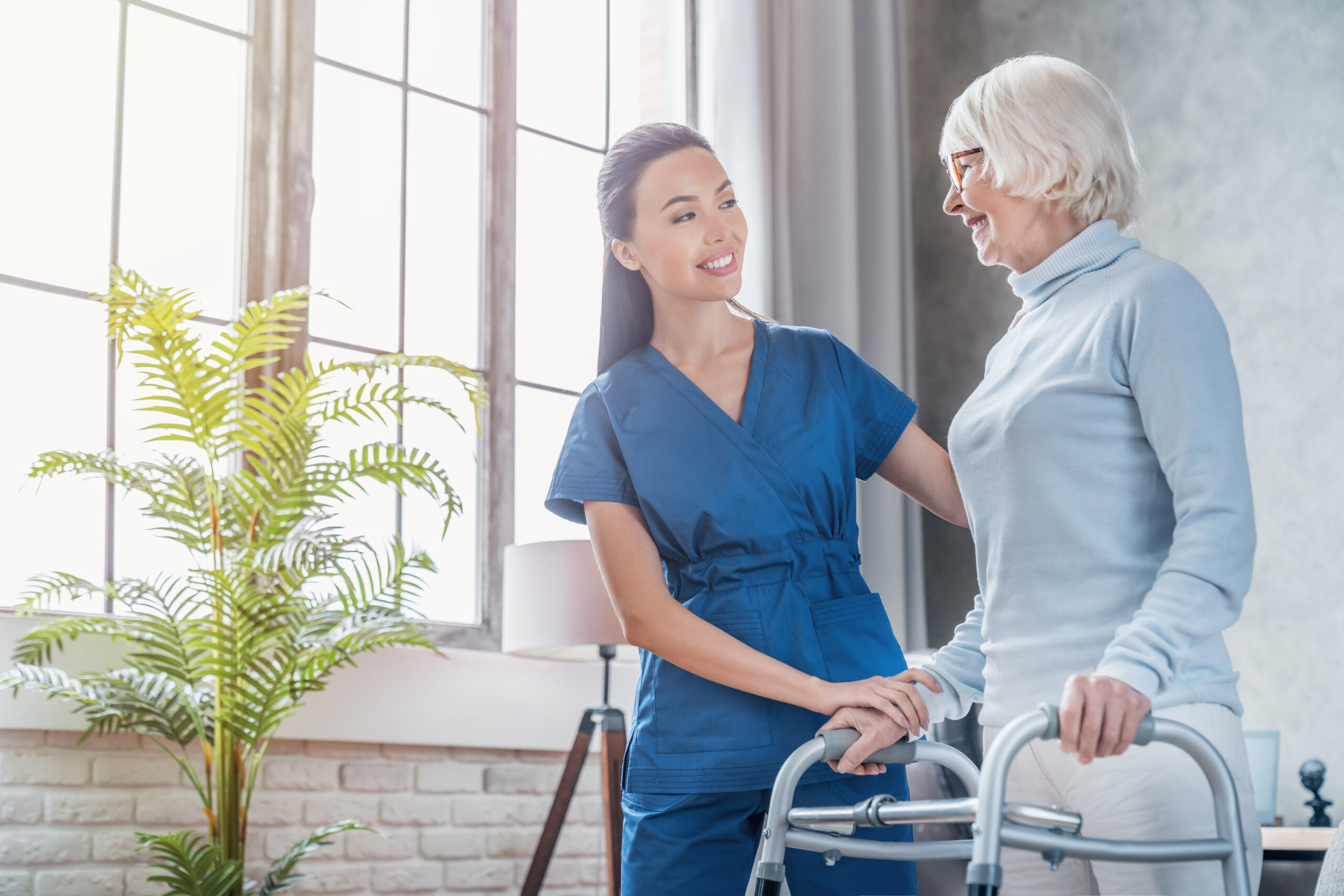 Young female social worker helping patient to walk with walker at home