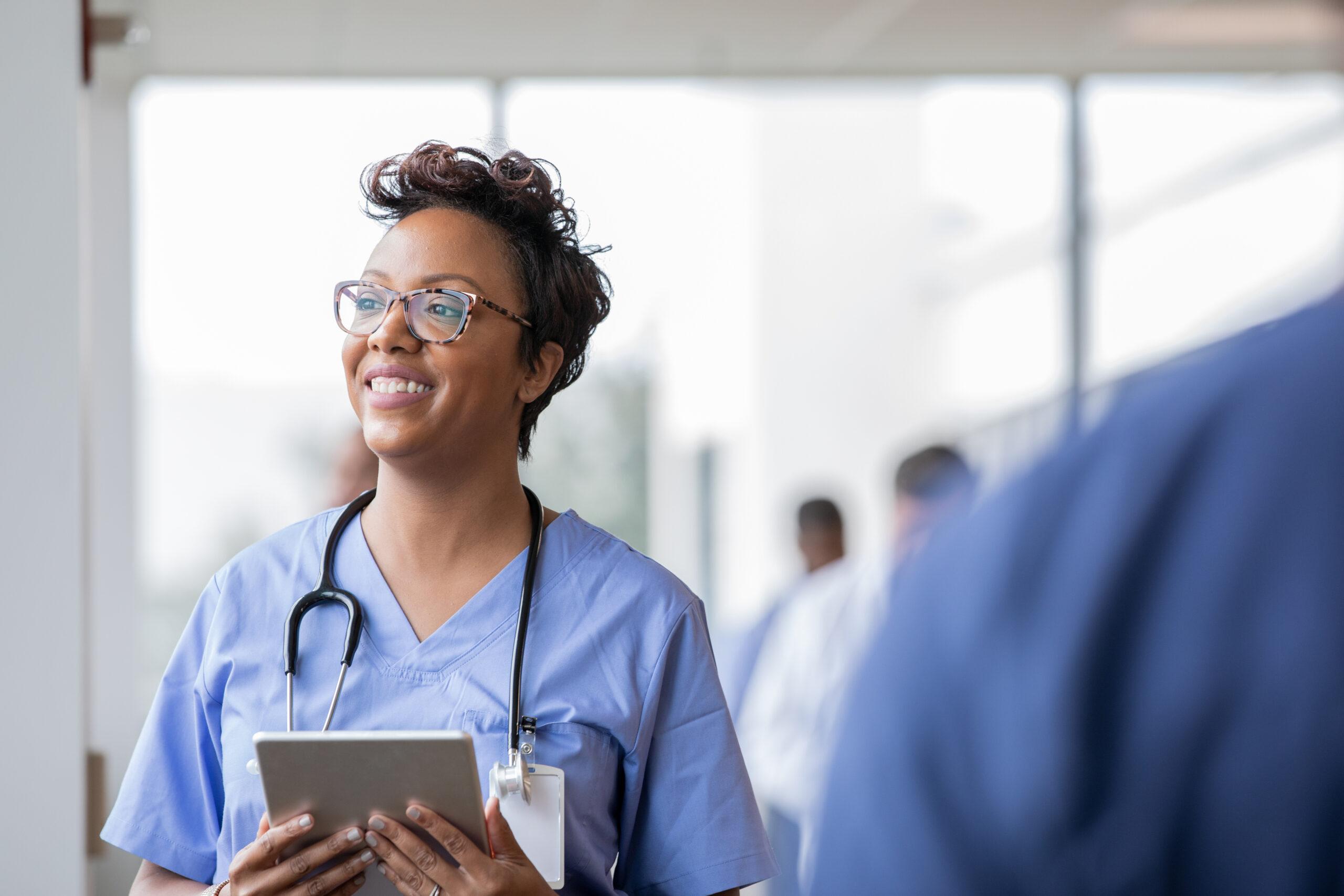 Nurse smiles while holding digital tablet