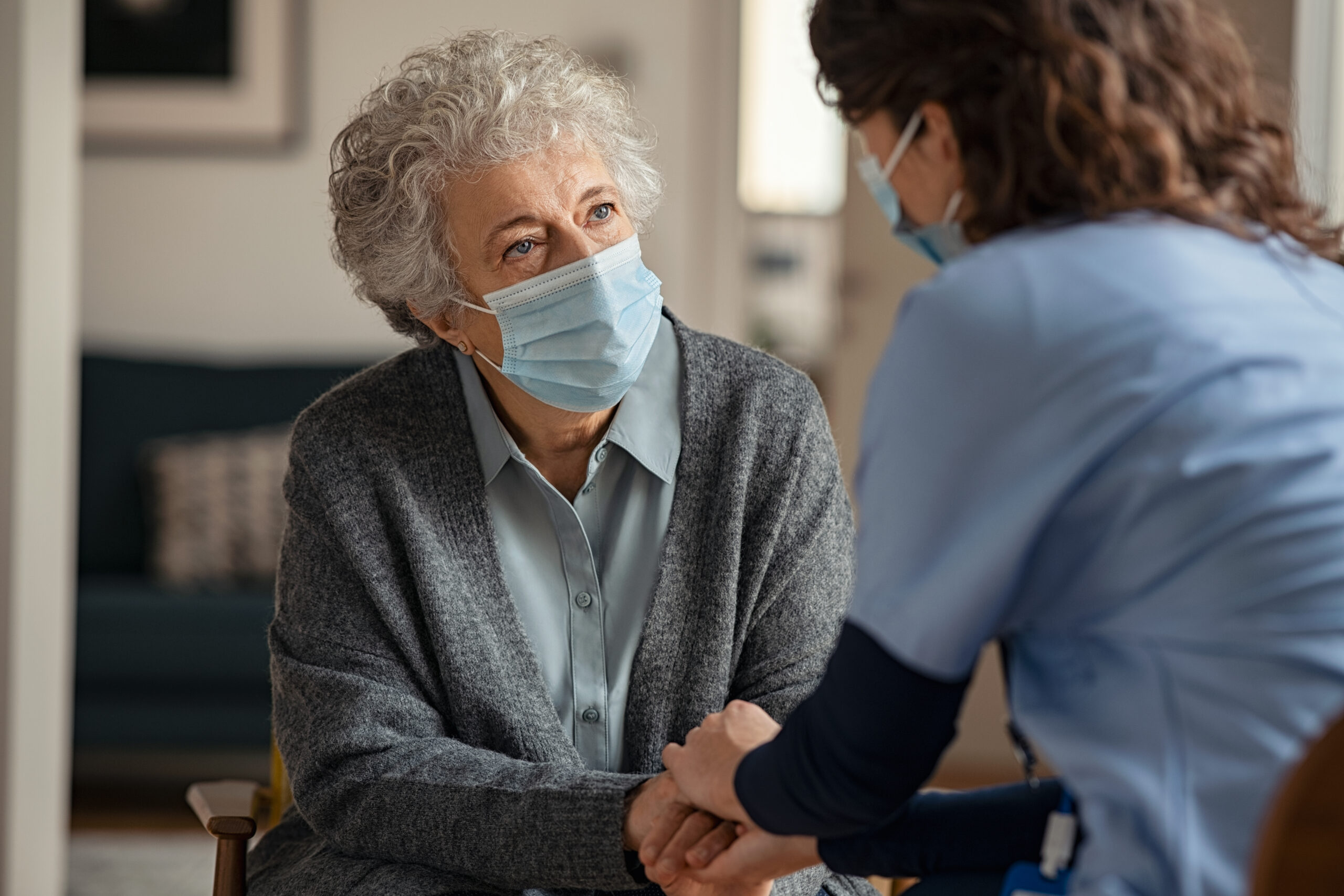 Female doctor consoling woman wearing face mask during home visit