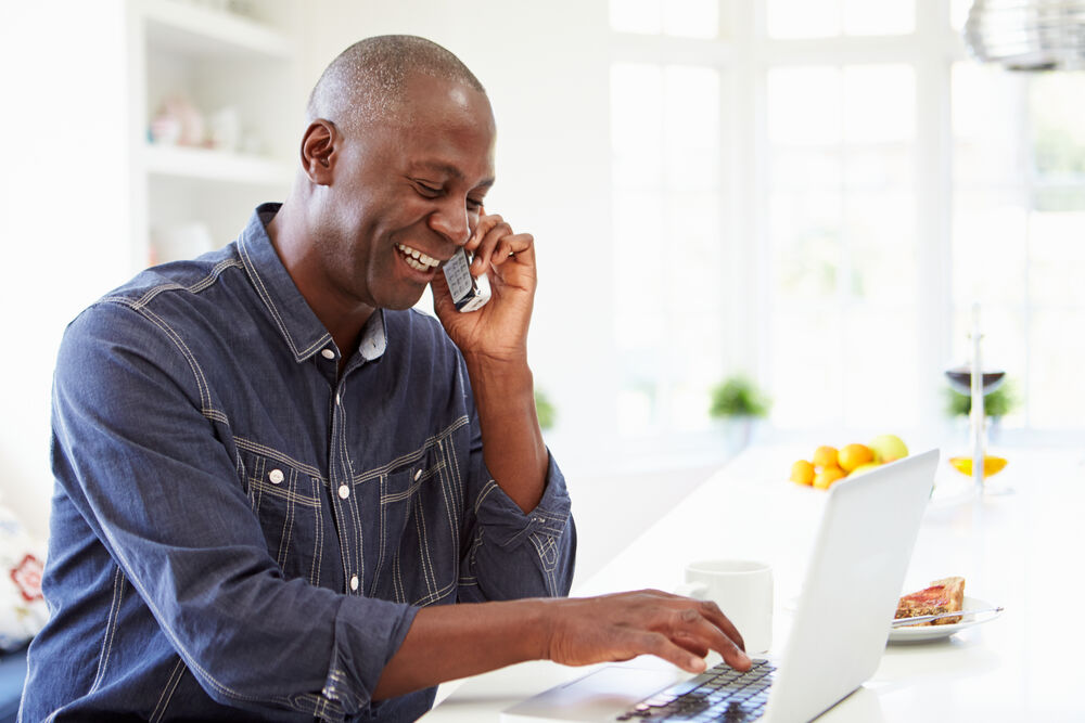 Man Using Laptop And Talking On Phone At Home