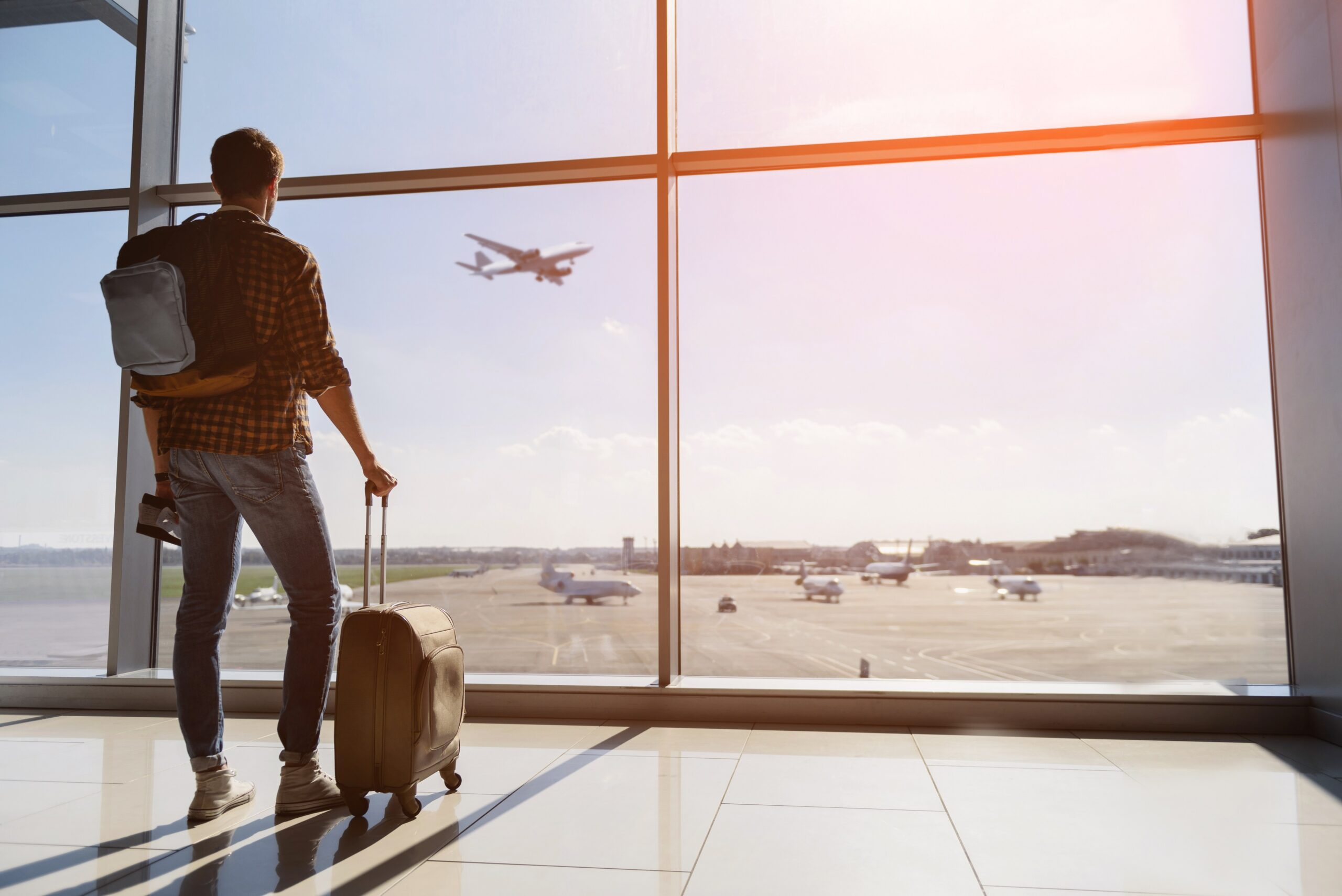 Young man watching plane before departure